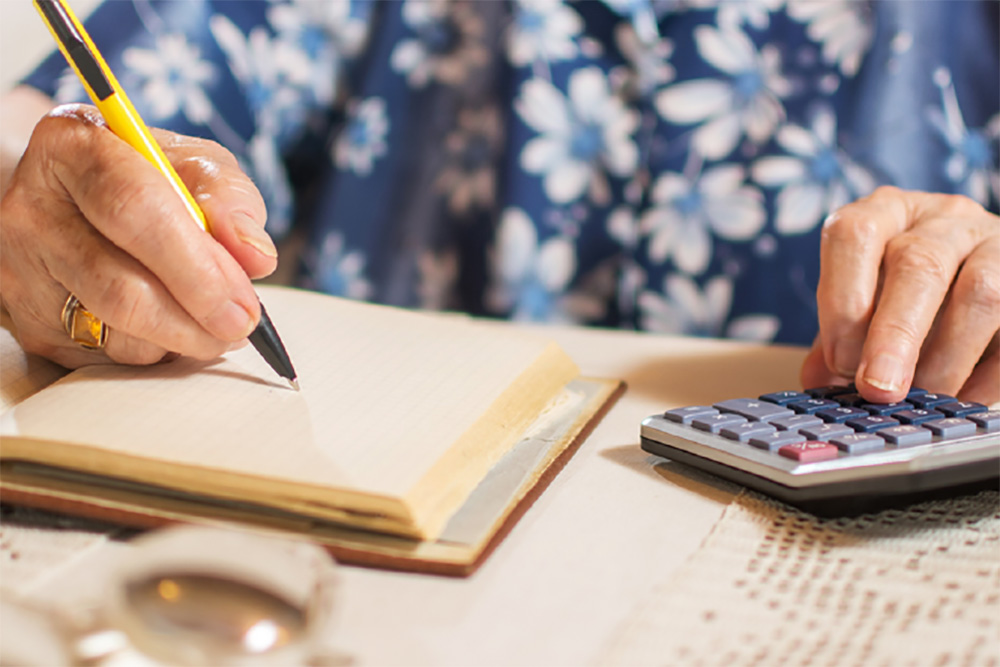 Person writing and calculating expenses.