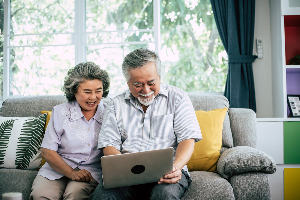 Older couple sitting with computer on the couch.