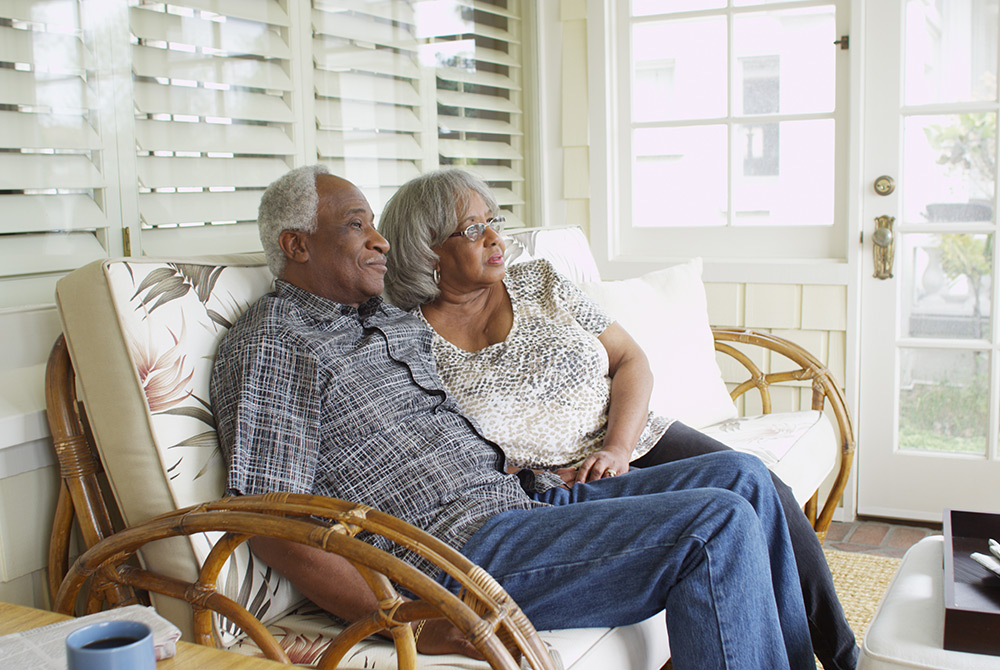 Elderly couple talking on the couch.