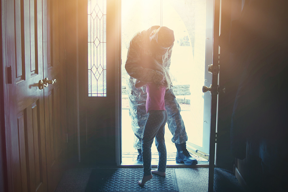 military serviceman hugging family