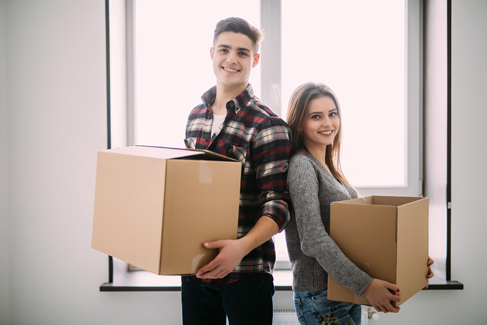 Couple with boxes moving into new home smiling.
