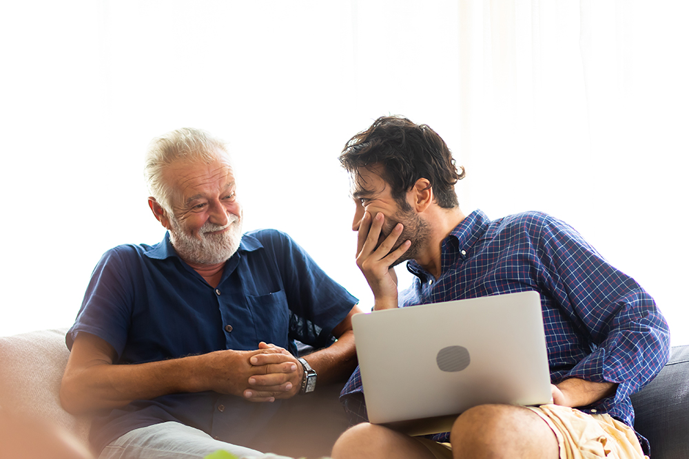 Smiling old father and happy son sitting on sofa using digital laptop computer.