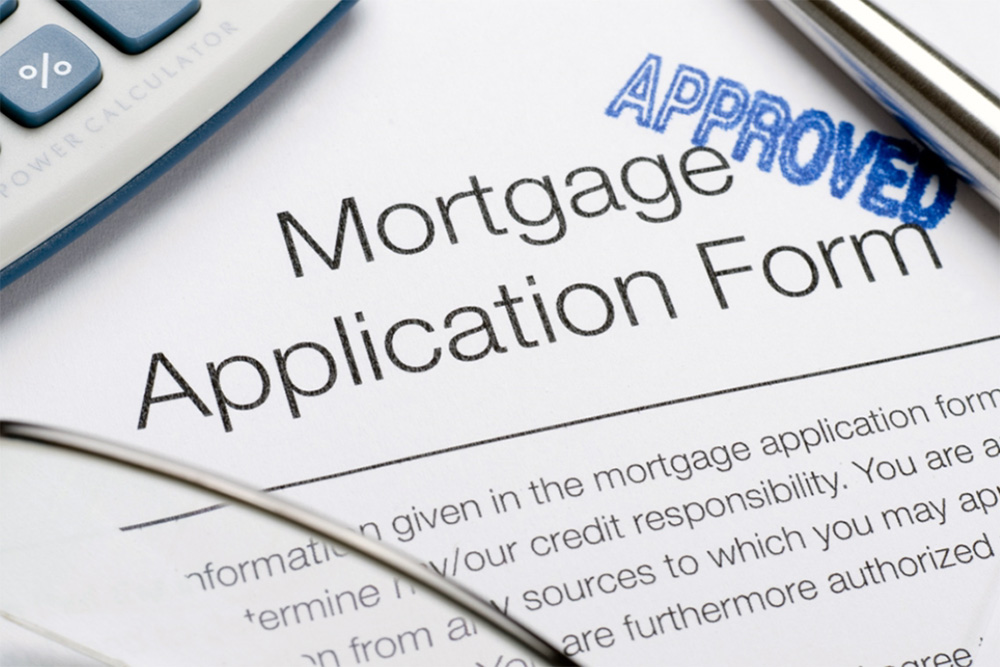 Mortgage application form and calculator with pen.