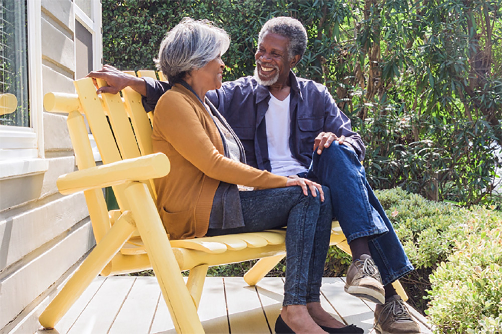 african american couple sitting outside on a bench