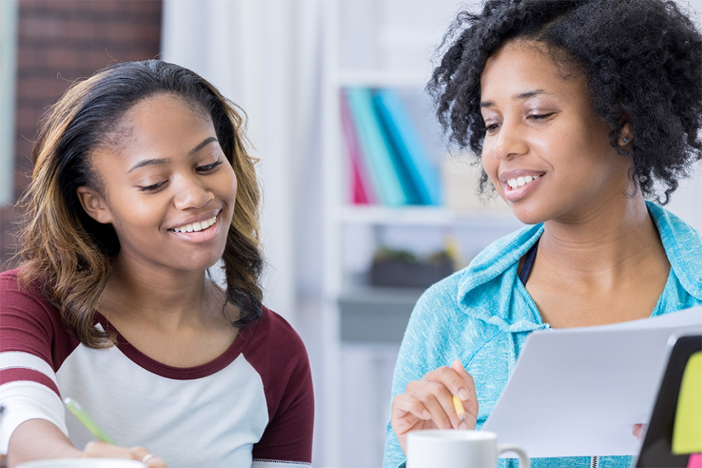 Mother and young daughter goign over papers